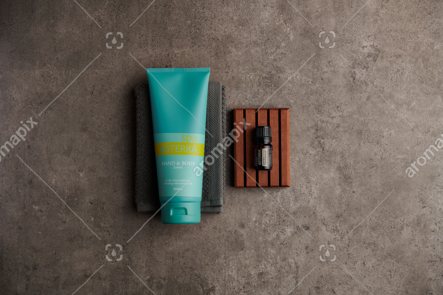 doTERRA Spa Hand and Body Lotion and Hawaiian Sandalwood essential oil on stone