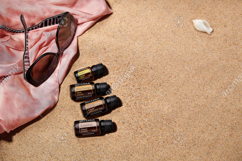 doTERRA Cheer, Wild Orange, Clove and Grapefruit with accessories on sand