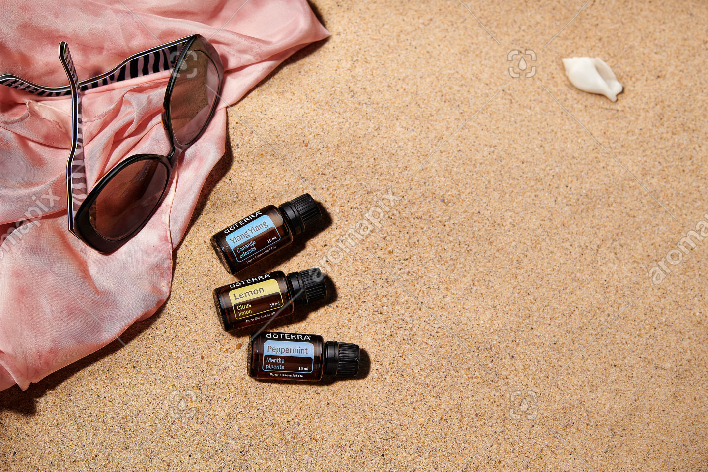 doTERRA Ylang Ylang, Lemon and Peppermint with accessories on sand
