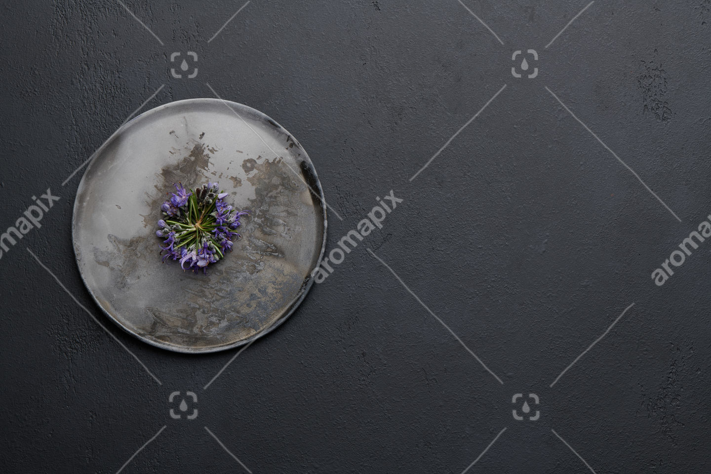 Rosemary flowers on a ceramic plate on black