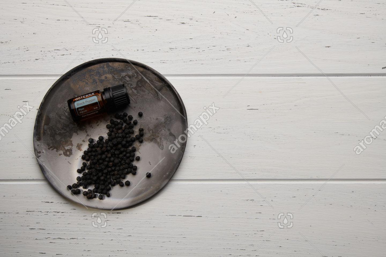 doTERRA Black Pepper with black peppercorns on white background