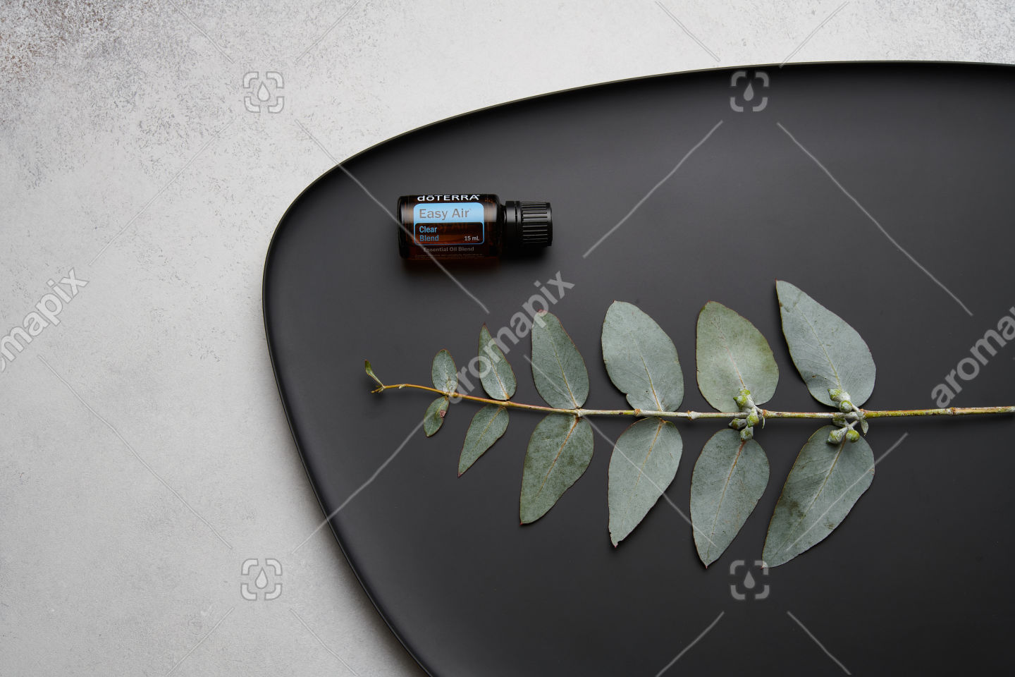 doTERRA Easy Air and eucalyptus leaves on black plate