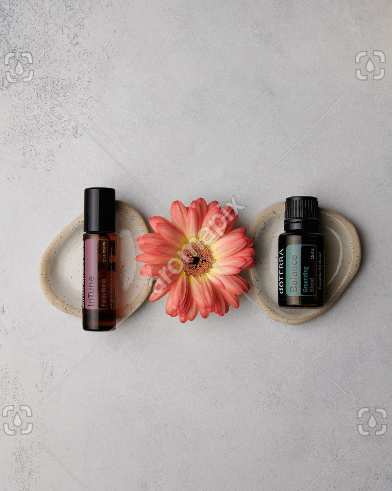 doTERRA InTune and Balance with a flower on concrete
