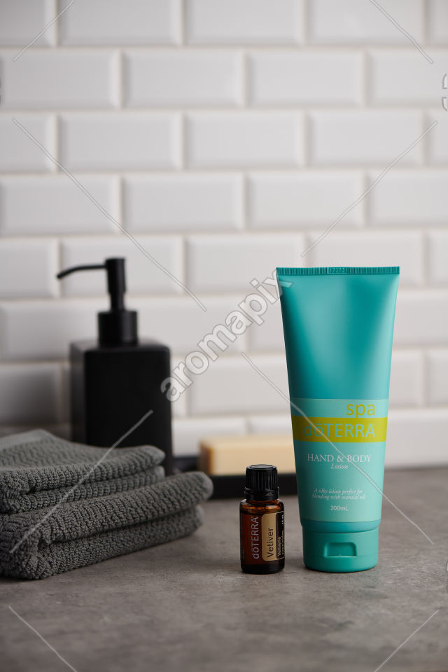 doTERRA Spa Hand and Body Lotion and Vetiver essential oil on stone bench