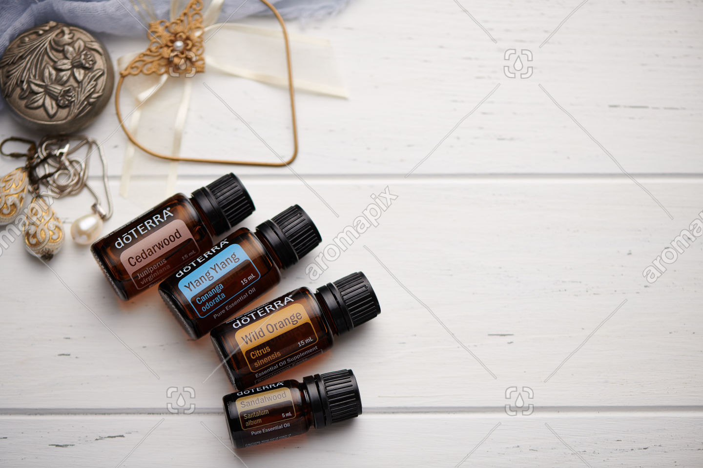 doTERRA Cedarwood, Ylang Ylang, Wild Orange and Sandalwood on white vintage wooden background