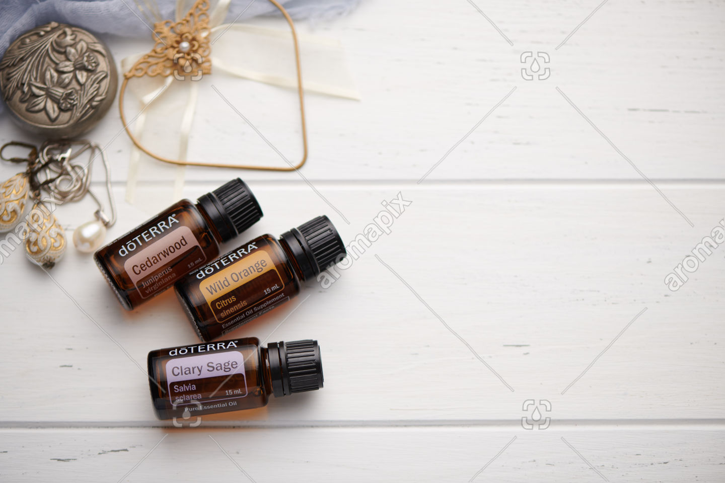 doTERRA Cedarwood, Wild Orange and Clary Sage on white vintage wooden background