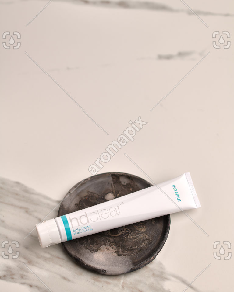 doTERRA HD Clear Facial Lotion on a ceramic plate on white marble