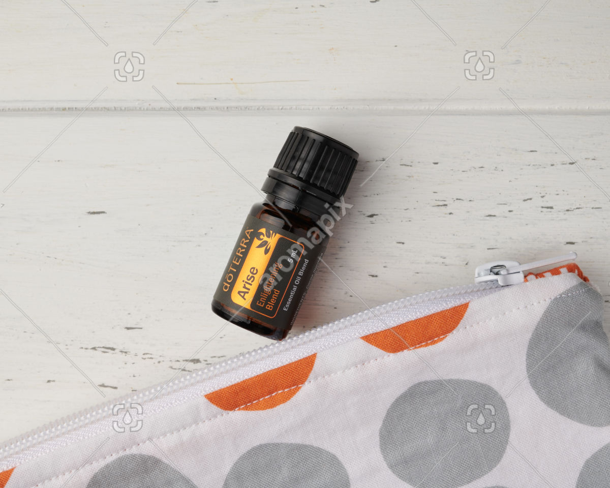 Close up of doTERRA Arise and the corner of an essential oil bag on white wood