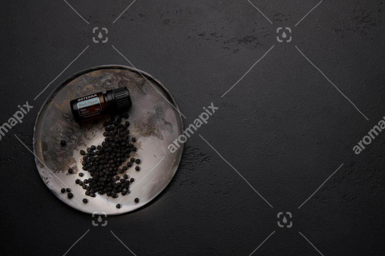 doTERRA Black Pepper with black peppercorns on black background