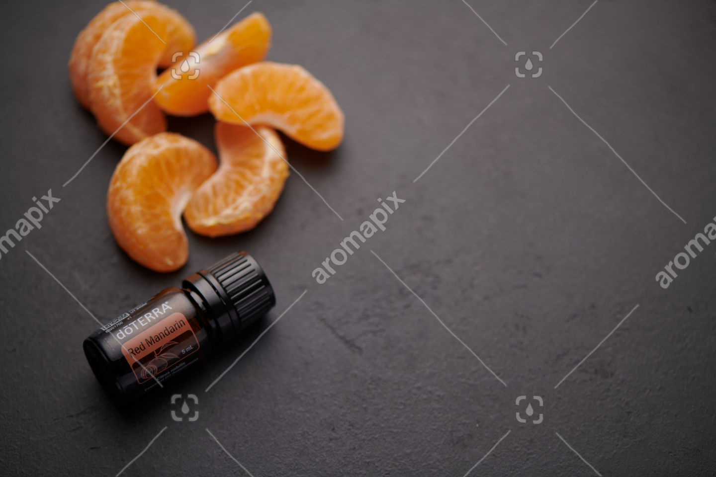doTERRA Red Mandarin product and mandarin pieces on black background