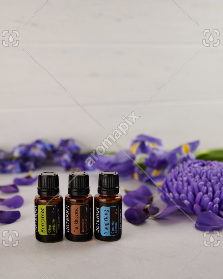 doTERRA Bergamot, Frankincense and Ylang Ylang with scattered purple flowers.