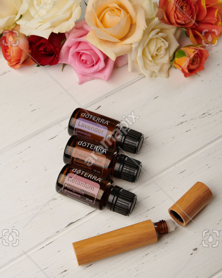 doTERRA Lavender, Frankincense and Geranium with roller bottle and roses on white