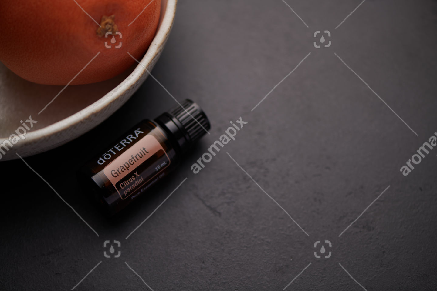 doTERRA Grapefruit product and fruit in white bowl