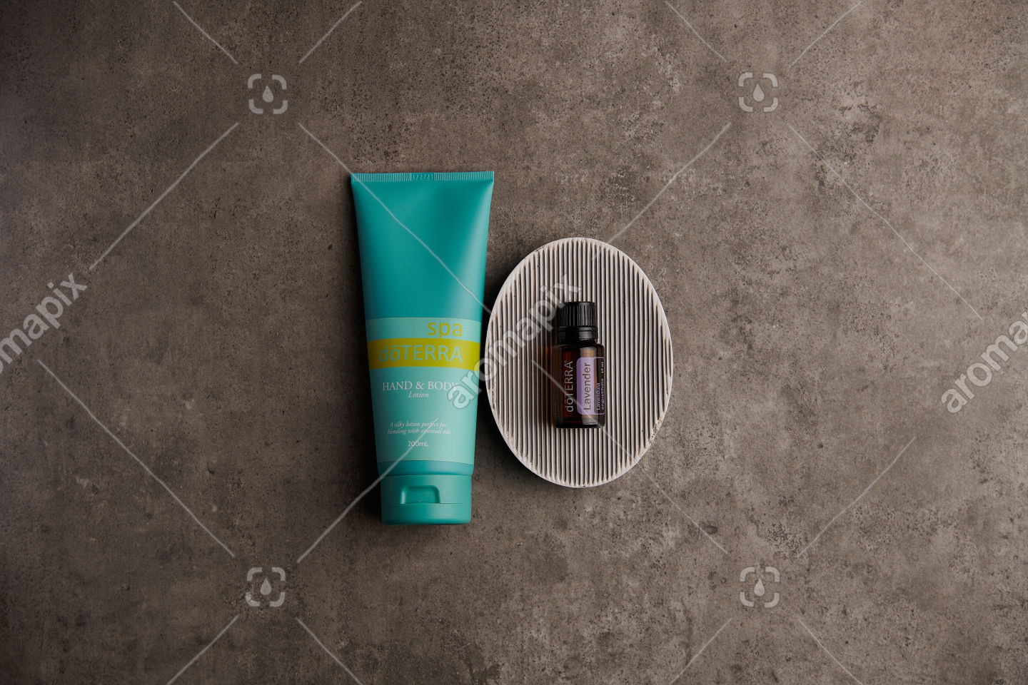 doTERRA Spa Hand and Body Lotion and Lavender essential oil on stone