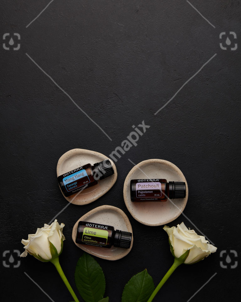 doTERRA Ylang Ylang, Patchouli and Lime with roses on black