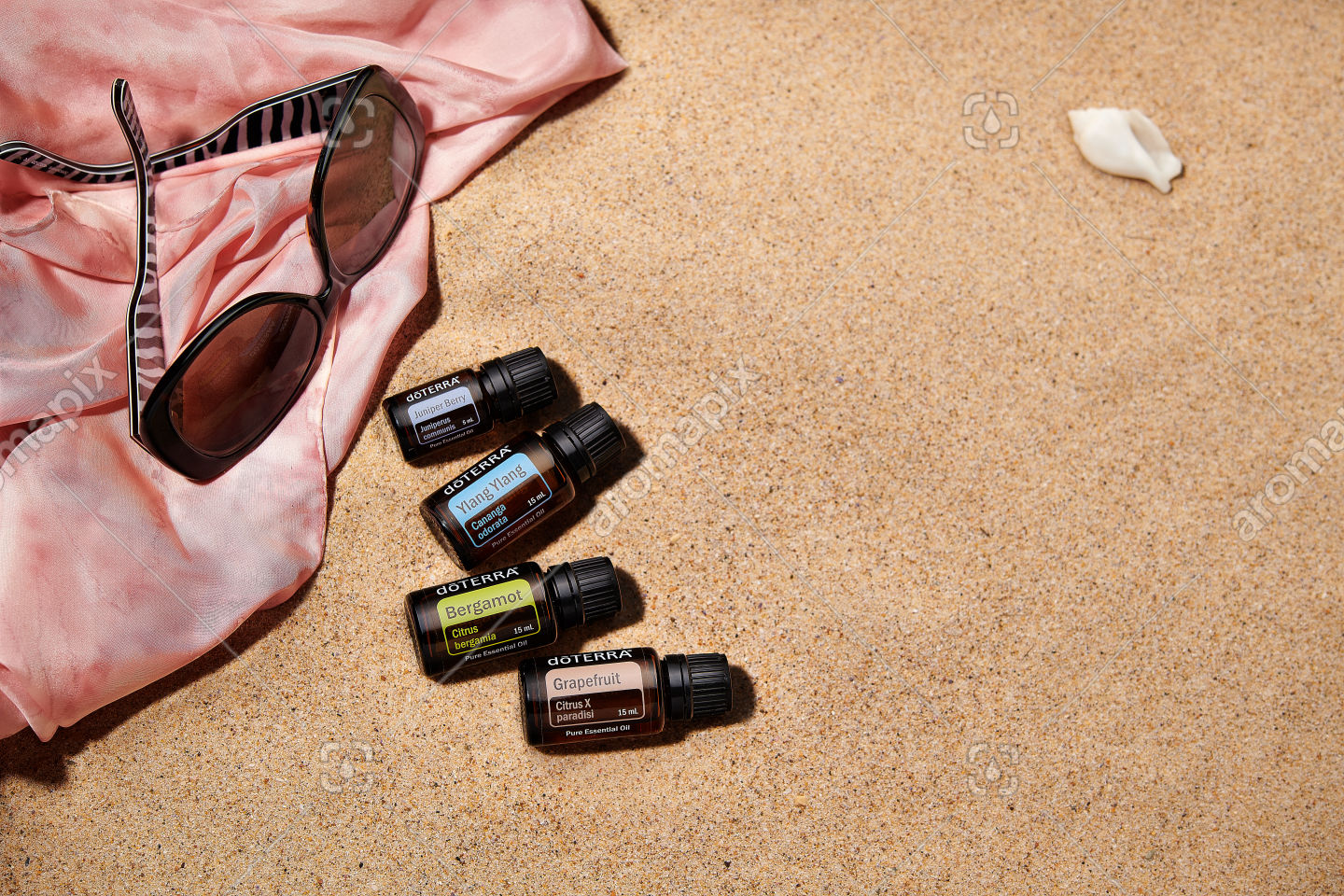 doTERRA Juniper Berry, Ylang Ylang, Bergamot and Grapefruit with accessories on sand