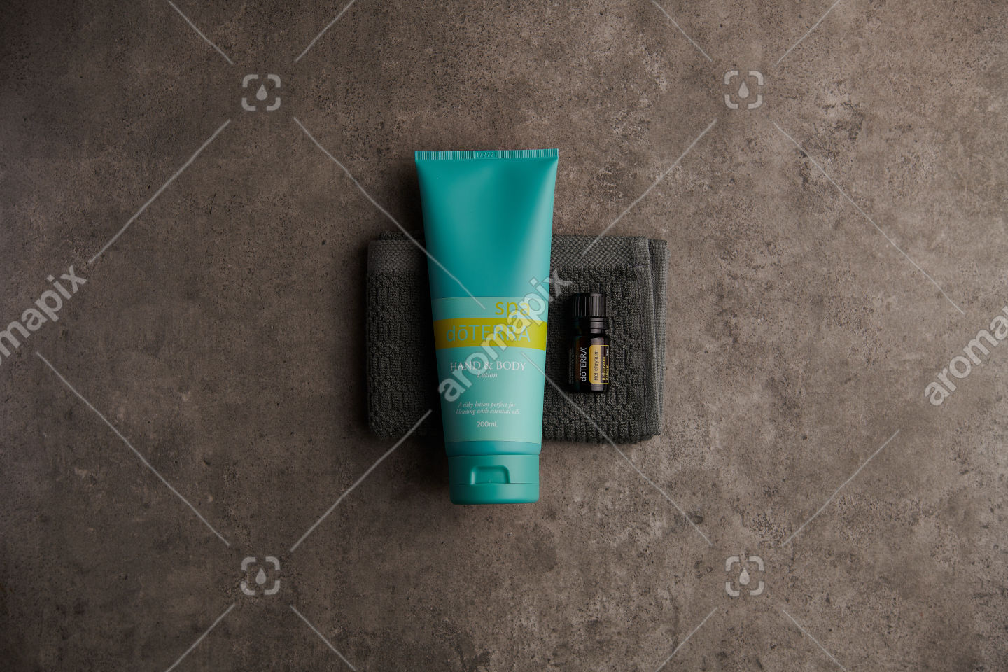 doTERRA Spa Hand and Body Lotion and Helichrysum essential oil on stone
