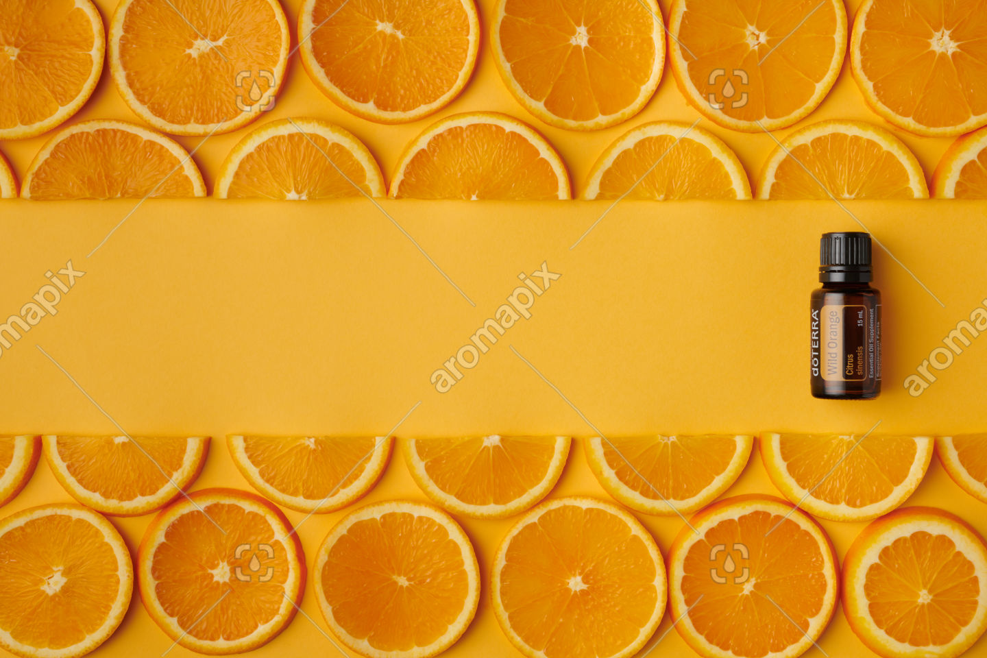 doTERRA Wild Orange product and orange slices on orange background