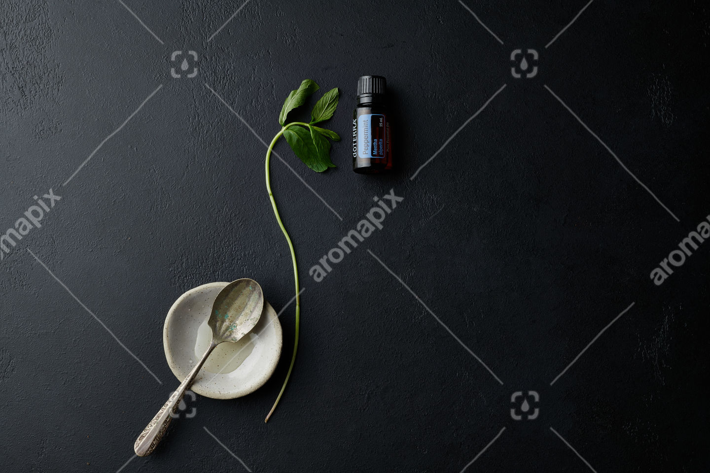 doTERRA Peppermint with utensils and a peppermint branch on black