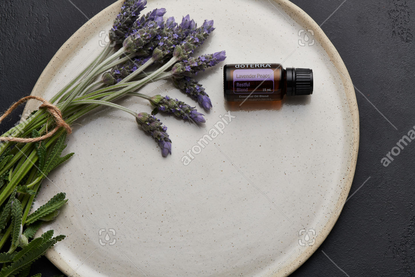 doTERRA Lavender Peace and lavender flowers on white ceramic plate with black background