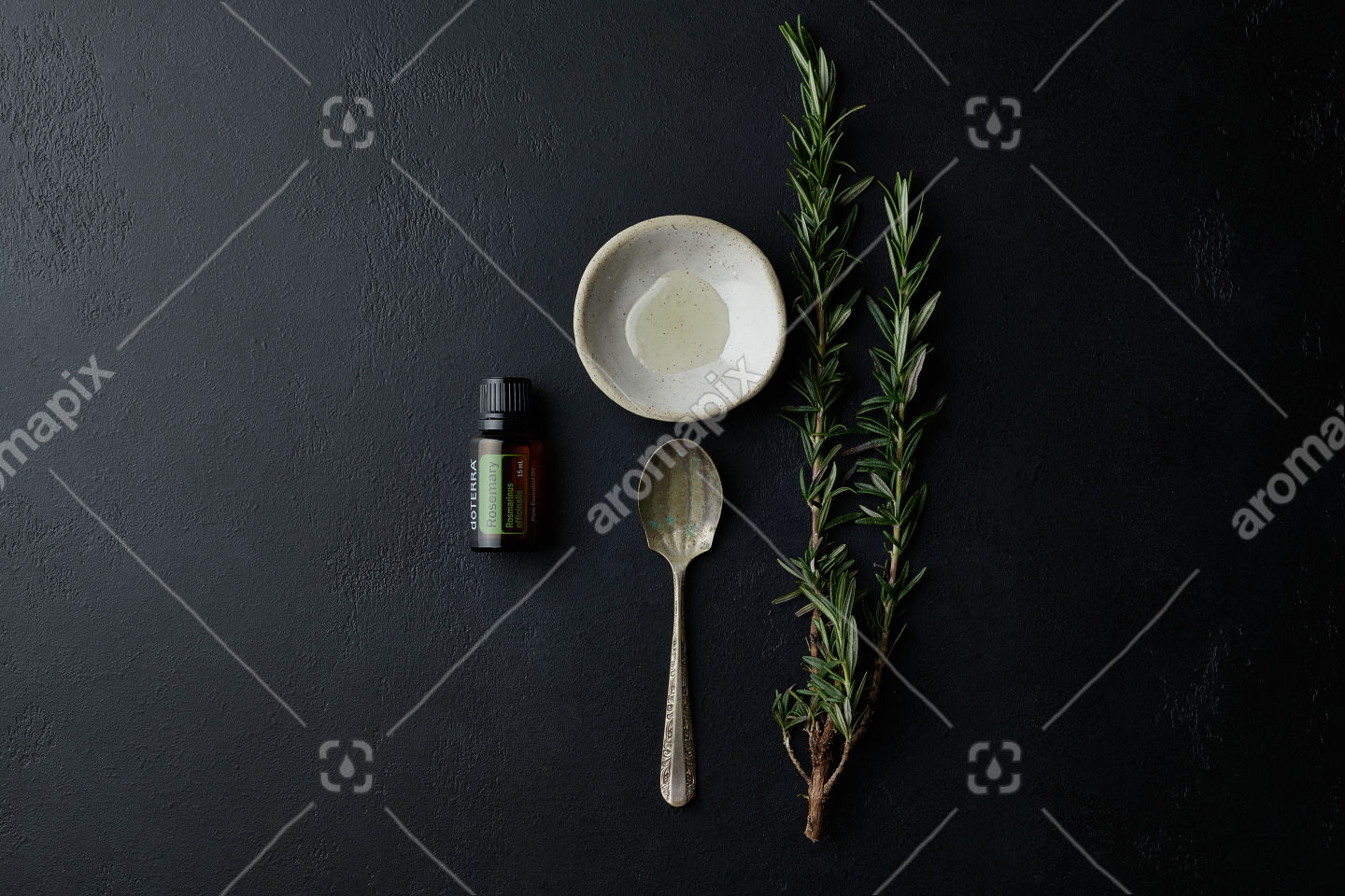 doTERRA Rosemary with kitchen utensils and a rosemary branch on black