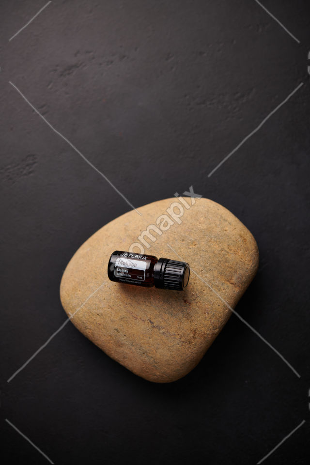 doTERRA Melissa on a stone on black