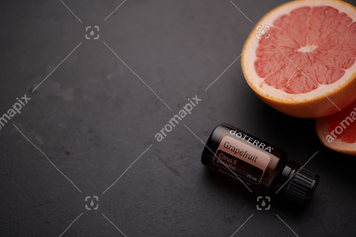 doTERRA Grapefruit product and grapefruit pieces on black background.