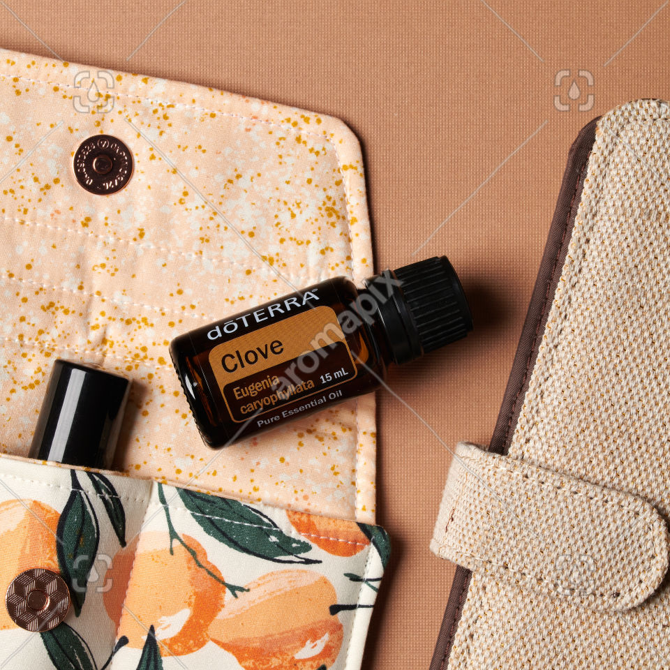 doTERRA Clove essential oil with accessories on brown