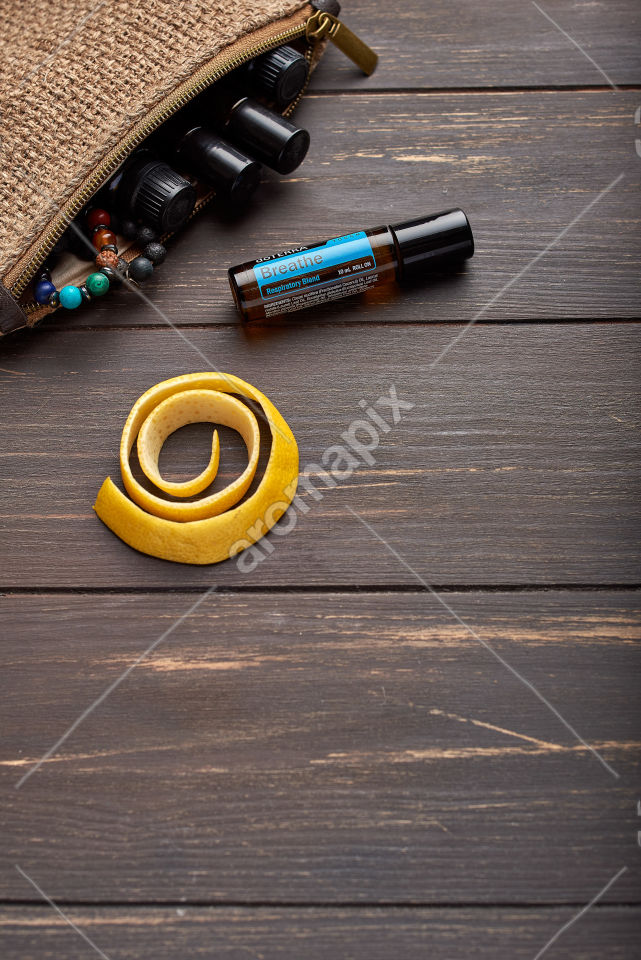 doTERRA Breathe Touch with lemon peel on wooden background