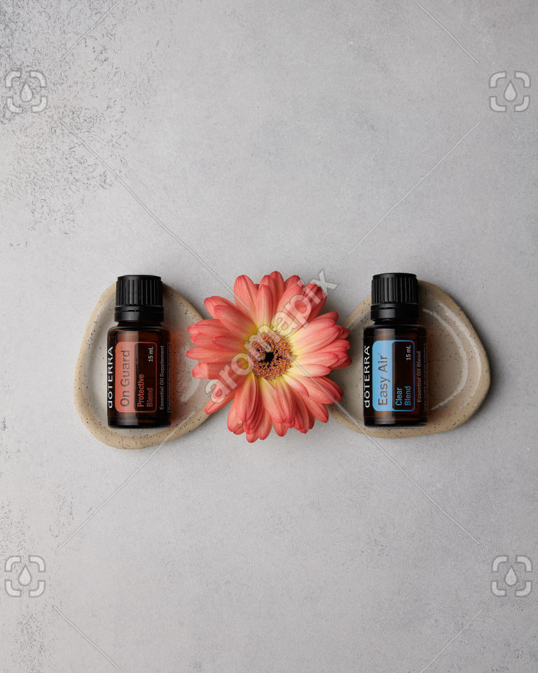doTERRA On Guard and Easy Air with a flower on concrete