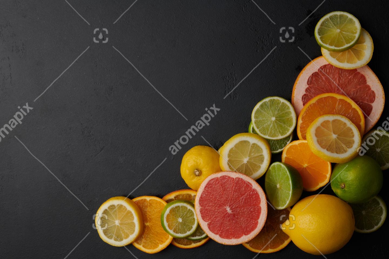 Lemon, orange, grapefruit and lime fruit on black concrete