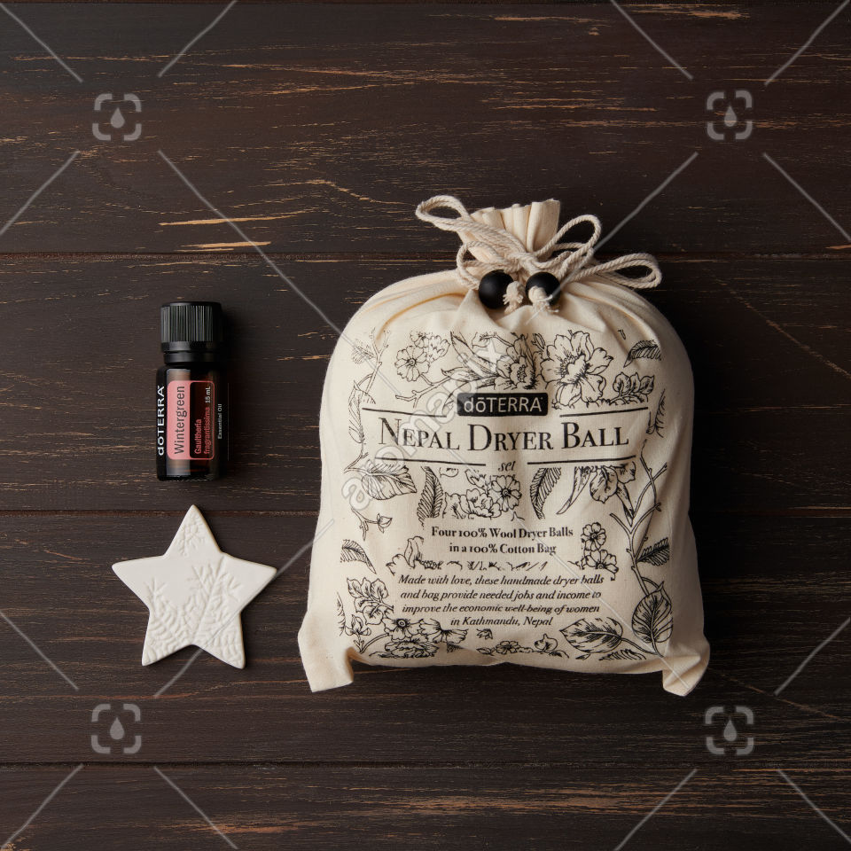 doTERRA Nepal Dryer Balls and Wintergreen essential oil with a star on brown