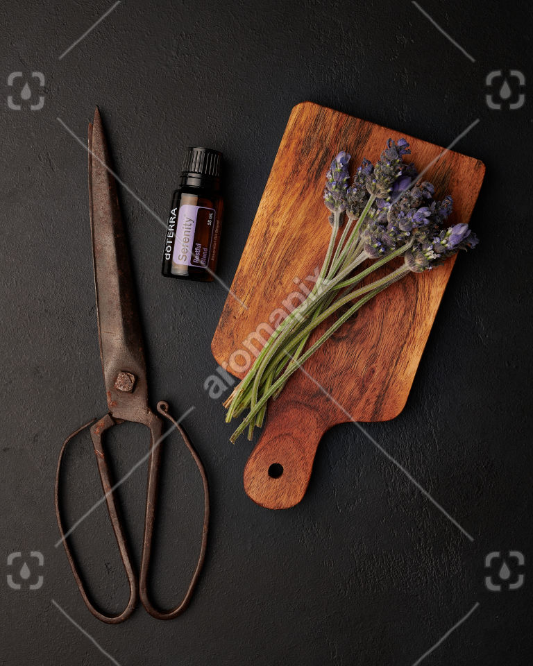 doTERRA Serenity with lavender flowers on a wooden board on black