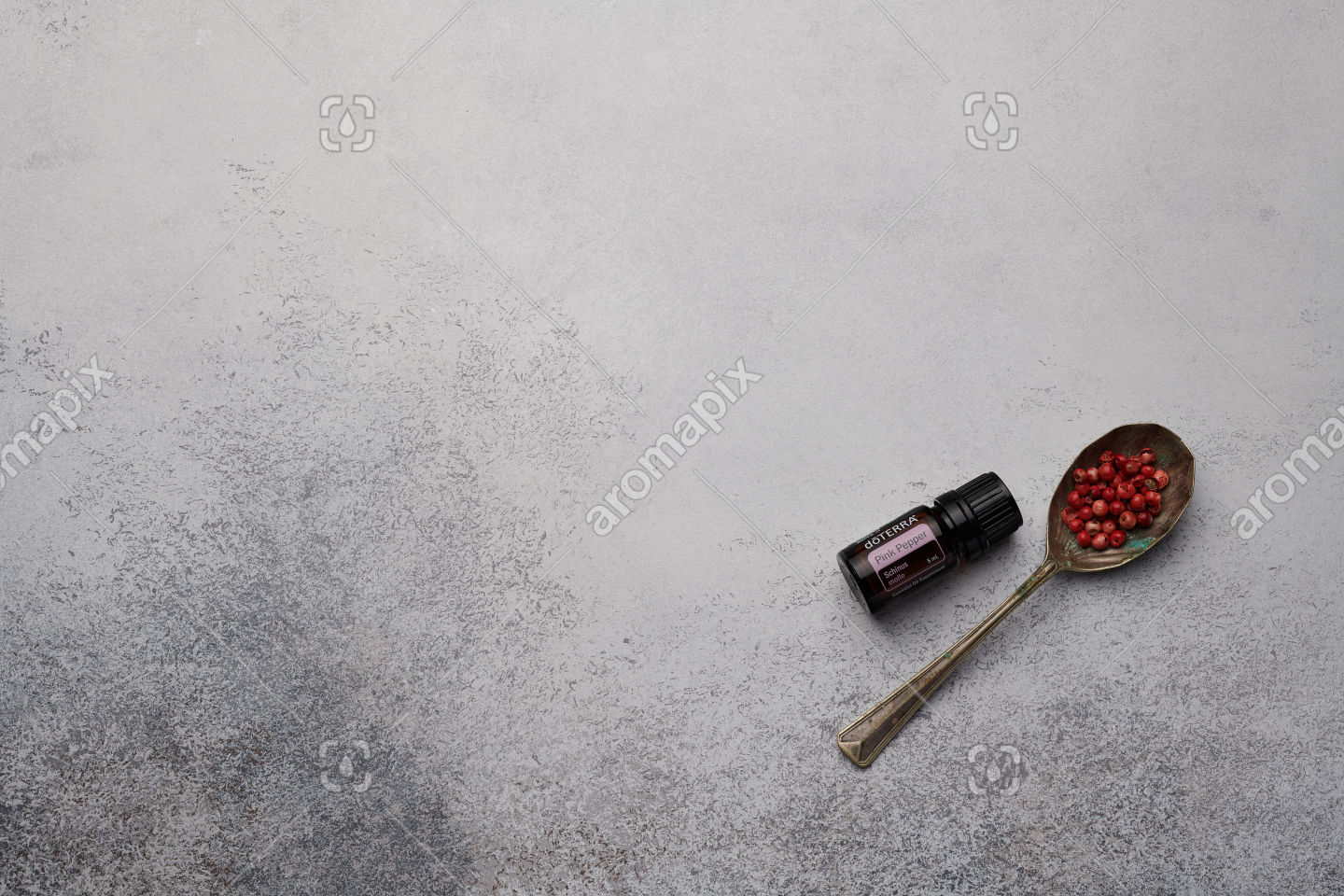 doTERRA Pink Pepper and pink peppercorns on white