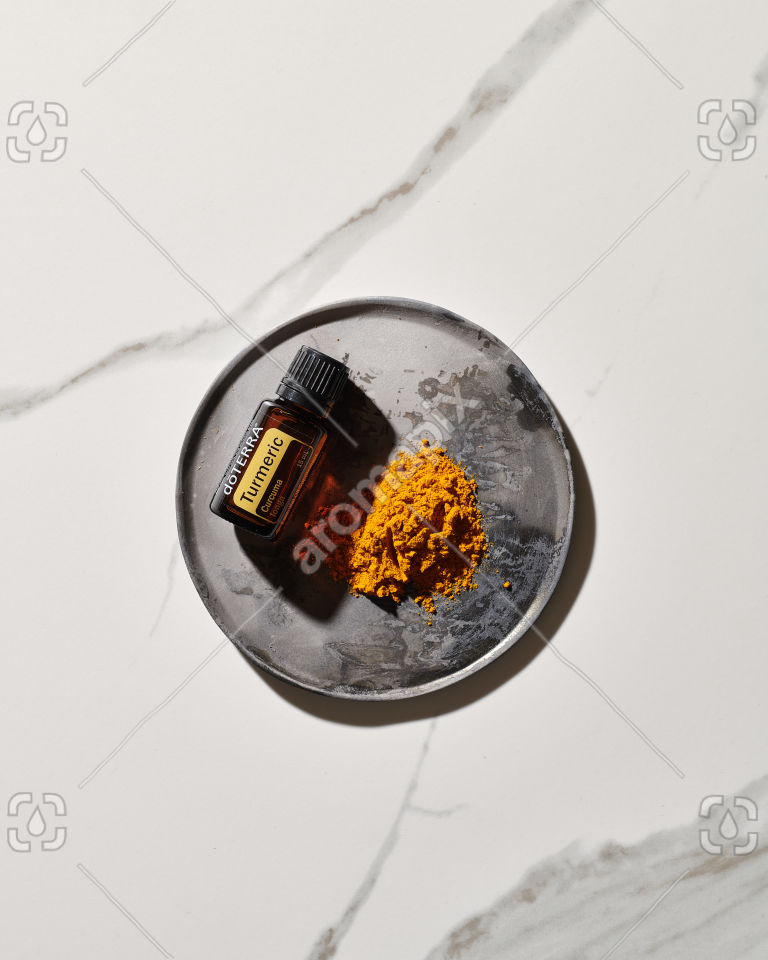 doTERRA Turmeric essential oil and ground turmeric on a ceramic plate in sunlight