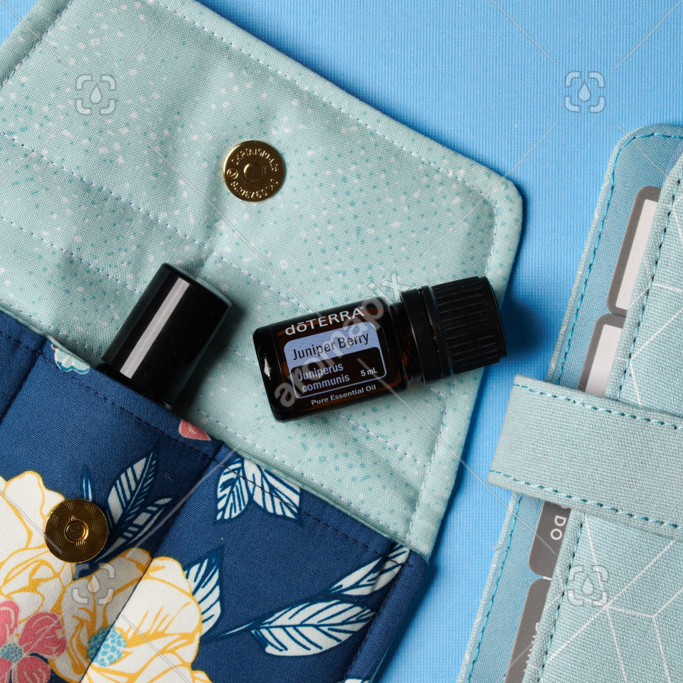 doTERRA Juniper Berry essential oil with accessories on blue