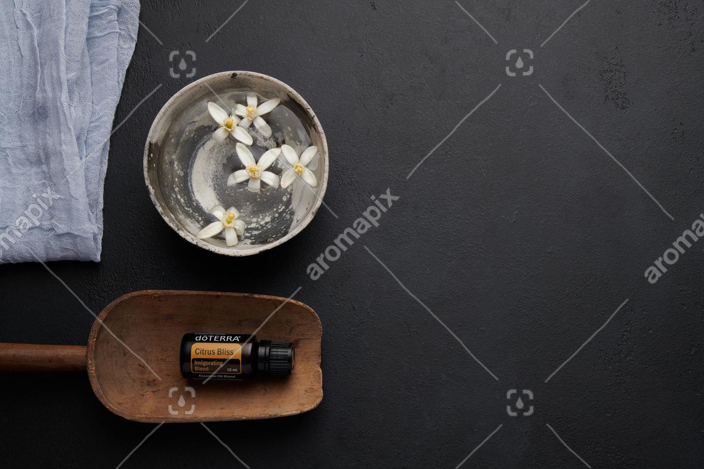 doTERRA Citrus Bliss in a wooden scoop with orange blosson on black