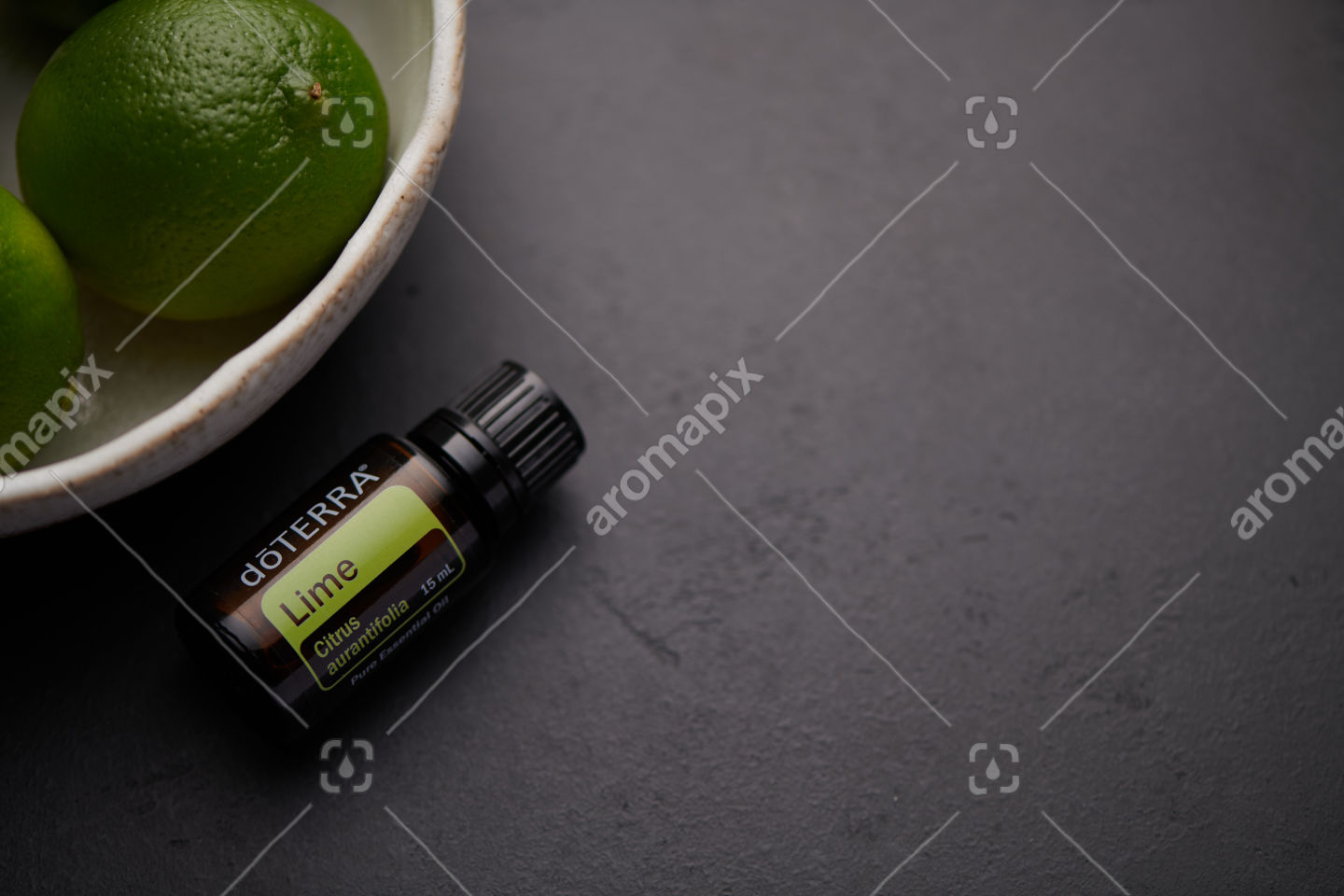 doTERRA Lime product and fruit in white bowl