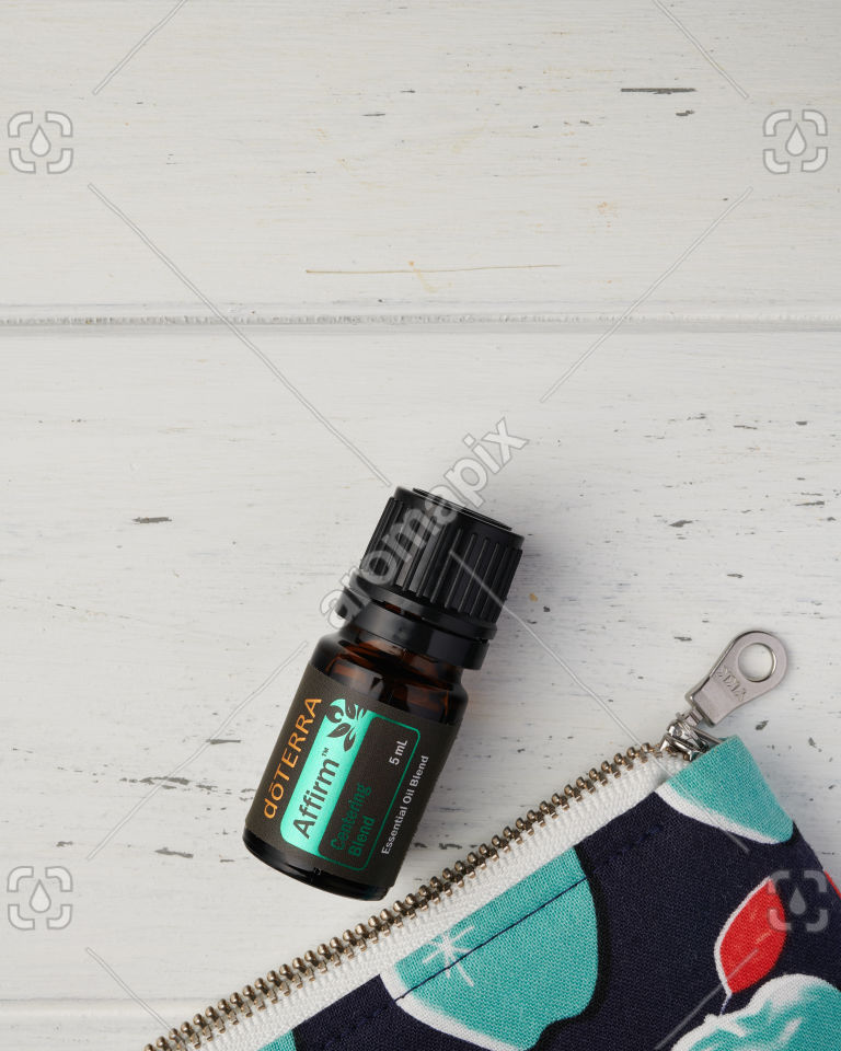 Close up of doTERRA Affirm and the corner of an essential oil bag on white wood
