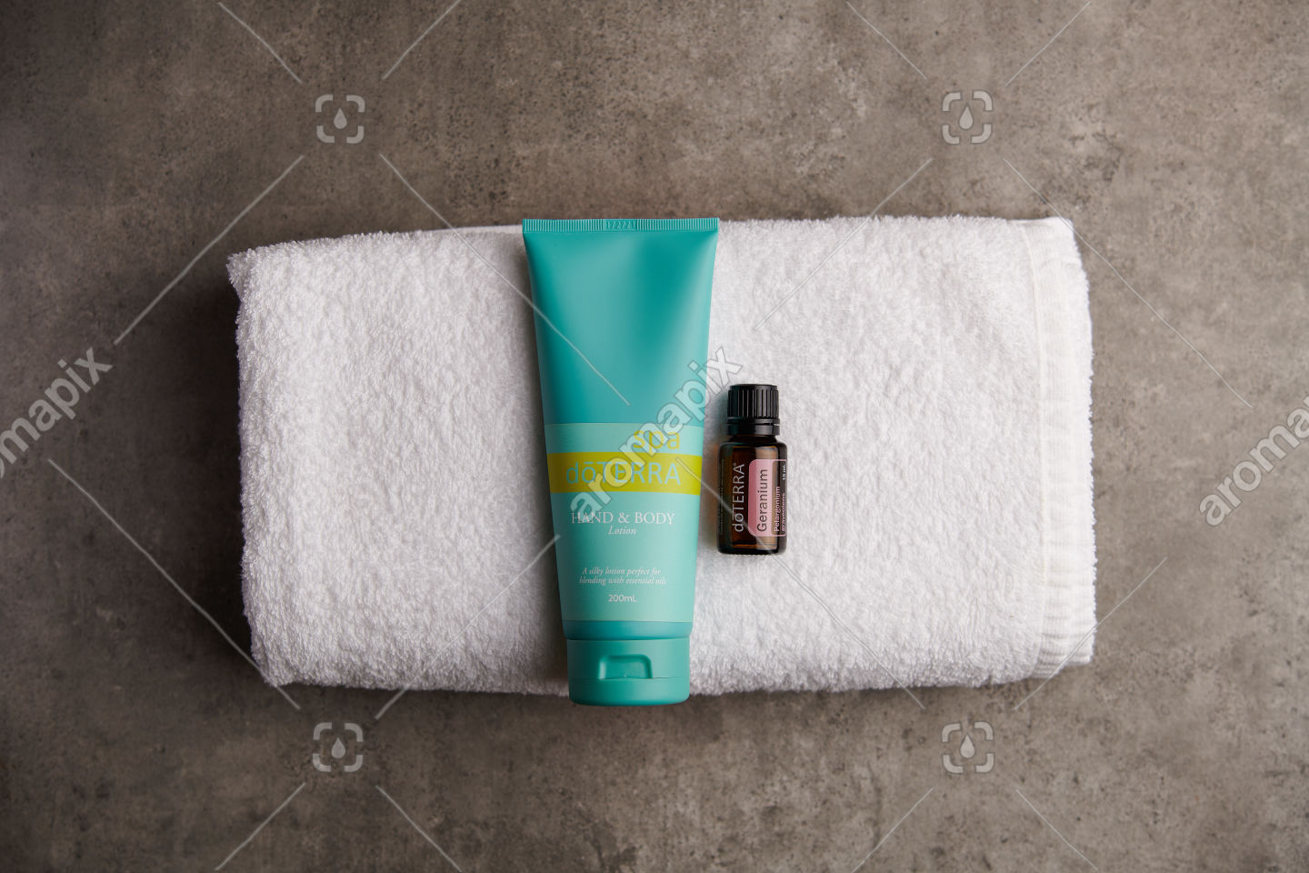 doTERRA Spa Hand and Body Lotion and Geranium essential oil on stone