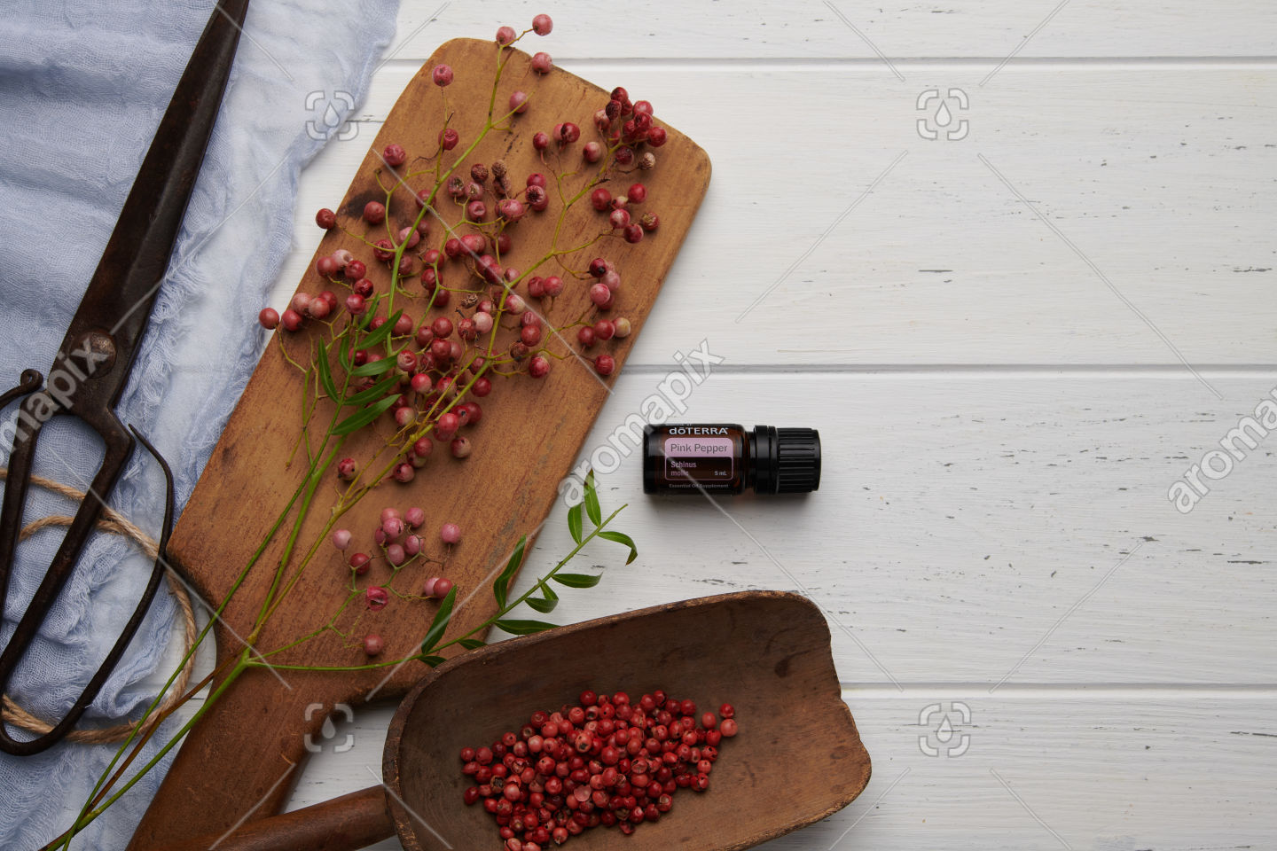 doTERRA Pink Pepper and pink peppercorns with utensils on white background