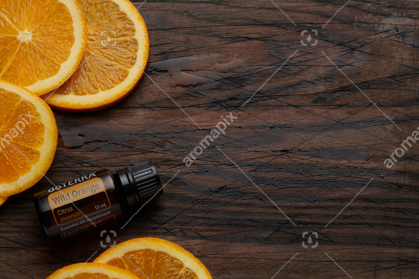 doTERRA Wild Orange product and orange slices on wooden board