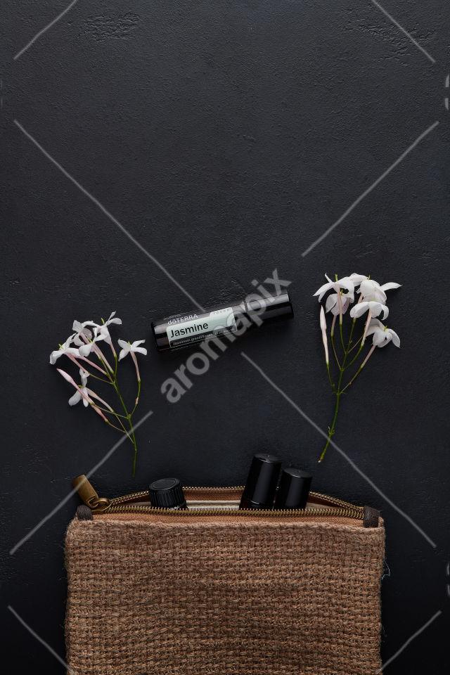 doTERRA Jasmine Touch with jasmine flowers on black