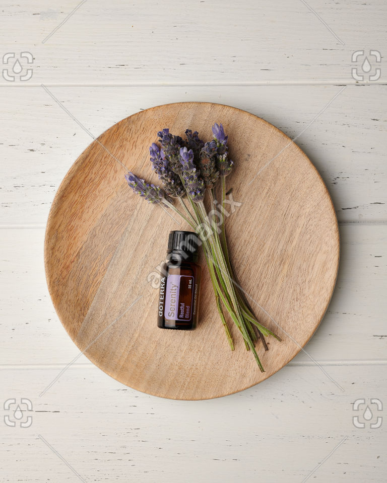 doTERRA Serenity and lavender flowers on a wooden plate on white