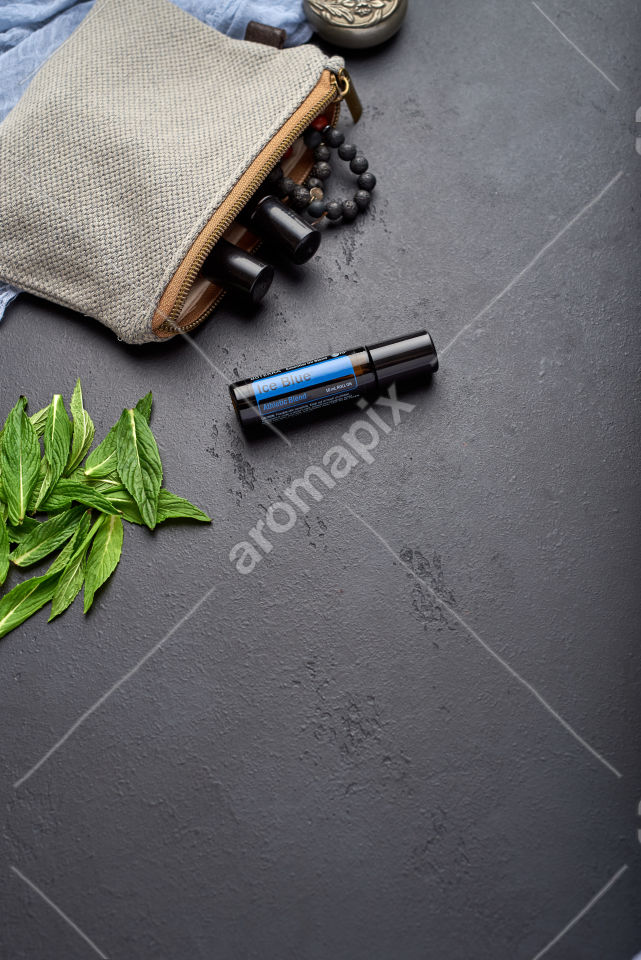 doTERRA Ice Blue Roll On with mint leaves on black