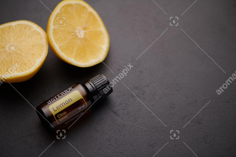 doTERRA Lemon product and lemon pieces on black background