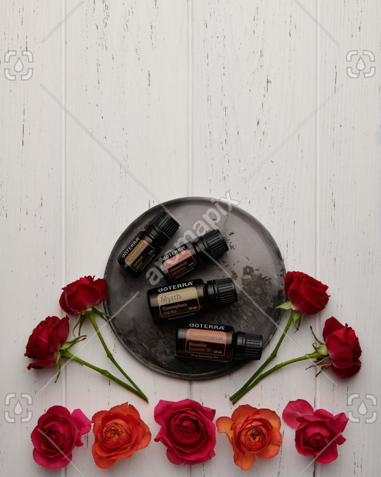 doTERRA Sandalwood, Cinnamon Bark, Myrrh and Frankincense with roses on white