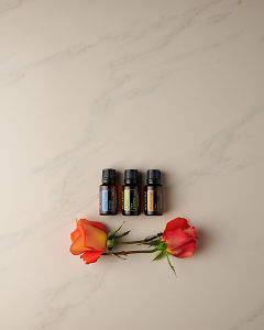 doTERRA Ylang Ylang, Lime and Wild Orange with rose stems on a white marble background.