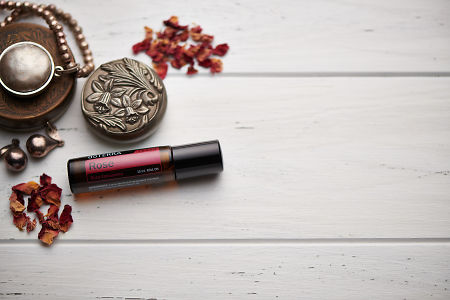 doTERRA Rose Touch, jewellery and trinkets on white rustic wooden background.