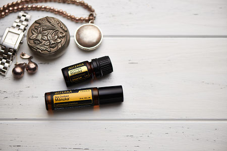 doTERRA Manuka oil and Manuka Touch, jewellery and trinkets on white rustic wooden background.